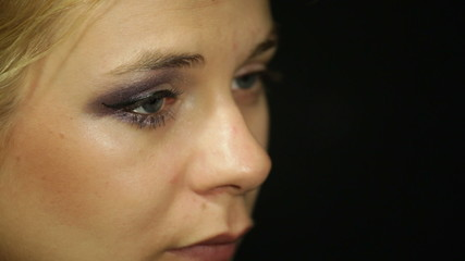 Detail of a young woman applying eye shadow makeup with cosmetic