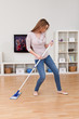 Young Woman Dancing While Cleaning Floor