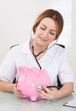 Female Doctor Examining Piggybank