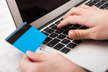 Person Using Credit Card For Online Shopping
