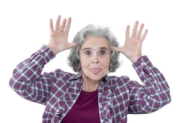 Seniorin macht Grimassen, streckt die Zunge raus & hat Spaß