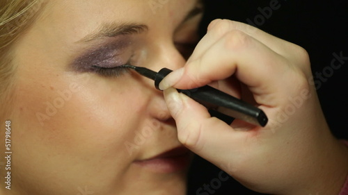 Detail of a young woman applying eye liner makeup