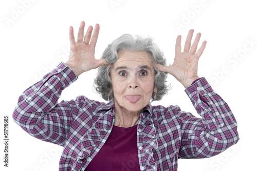 canvas print picture Seniorin macht Grimassen, streckt die Zunge raus & hat Spaß