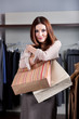 Woman embraces paper bags full of pleasant clothes