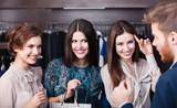 Three wonderful women flirt with salesperson