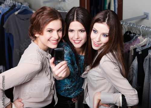 Three girls photo session on the mobile phone after shopping