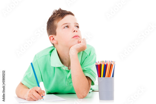 Dreaming boy lying on the floor and drawing with colorful pencil