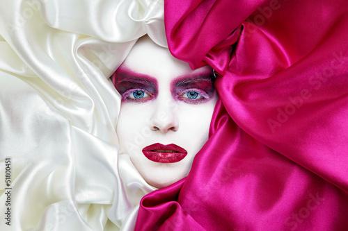 Hübsche Frau mit tollem Make Up liegt in Satin