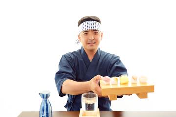 寿司を差し出す笑顔の寿司職人