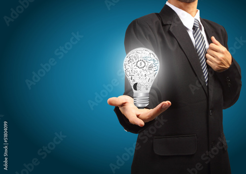 Business man holding Light bulb with drawing graph inside