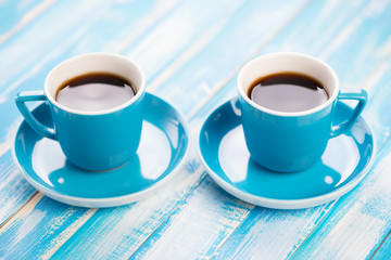 Pair of espresso cups on wooden boards, horizontal shot