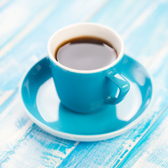 Cup of black coffee on wooden boards, close-up