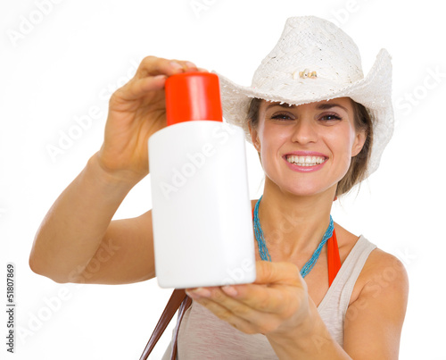 Smiling beach young woman showing sun block creme