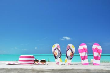 Hat, sunglasses and flip-flops on the beach of Exuma, Bahamas