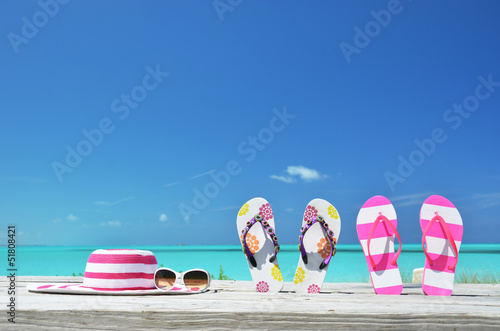 Hat, sunglasses and flip-flops on the beach of Exuma, Bahamas