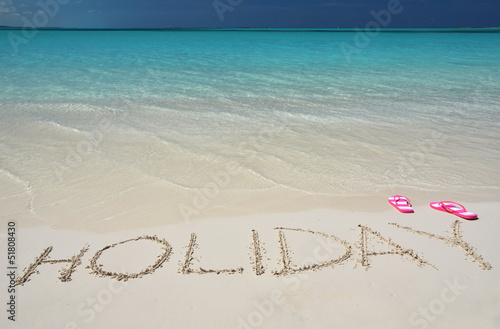 HOLIDAY writing on the sandy beach
