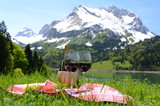 Fototapety Wine and fruits served at a picnic in Alpine meadow. Switzerland