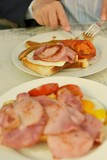 breakfast with fried eggs, hams, toasts and grilled tomatoes