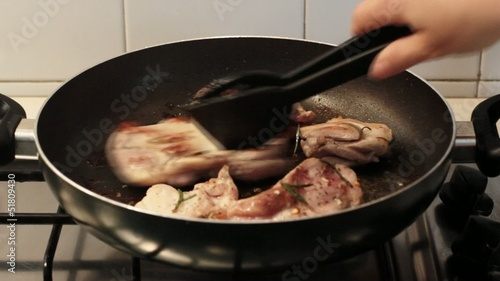 chef cooking chicken with herbs