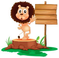 A lion above a trunk beside a wooden signboard