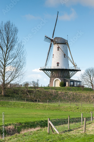 White windmill on top of the dike