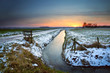 sunset reflected in frozen canal