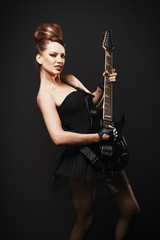 Rock female with guitar over dark background.