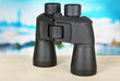 Black modern binoculars on wooden table on blue background