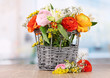 Many different flowers in basket on room background