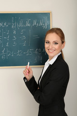 Portrait of teacher woman near the chalkboard in classroom