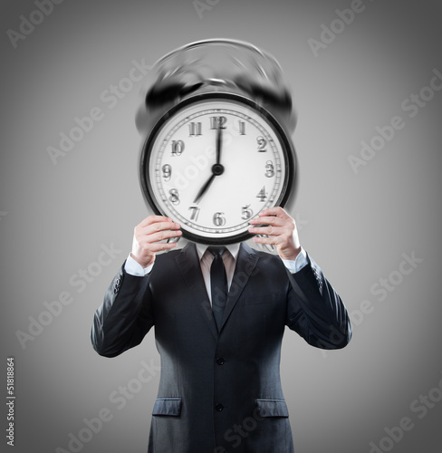 Businessman with ringing alarm clock on head