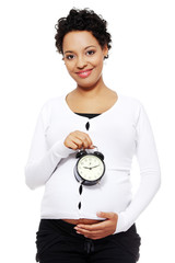 Pregnant woman with alarm clock