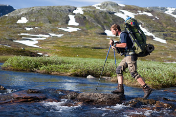 Wanderer beim überqueren von Stromschnellen in Norwegen