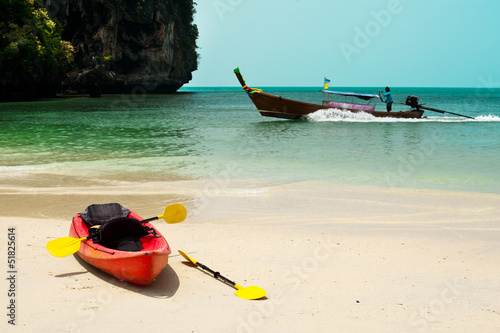 Tropical beach landscape with red canoe boat at ocean coast