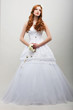 Sensuality. Fiancee in White Long Dress with Bouquet of Flowers