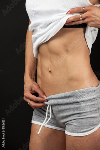 Closeup view of a fitness young woman over black