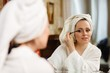 Woman applying mascara for eyelashes.