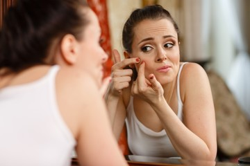 .Woman finding an acne on her cheek
