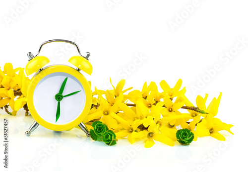 Spring concept with clock and yellow flowers
