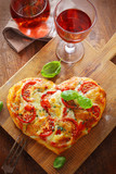 Heart shaped pizza with red wine