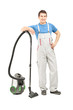 Full length portrait of a man in uniform posing with a vacuum cl