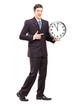 Full length portrait of a youn man in suit pointing on a clock
