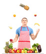 Man juggling with fruits behind a table full of fruits and veget