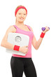 Young female holding a dumbbell and a weigth scale