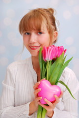 beautiful young girl with pink tulips and heart