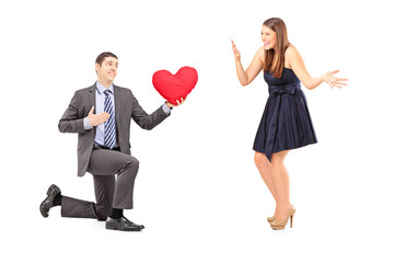 Romantic man giving a red heart to a young woman