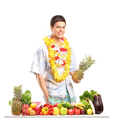Man holding a pinneapple and posing behind a table with fruits a