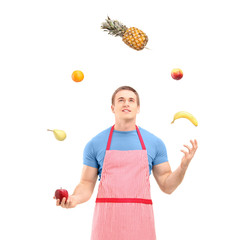 Young man in apron juggling with fruits