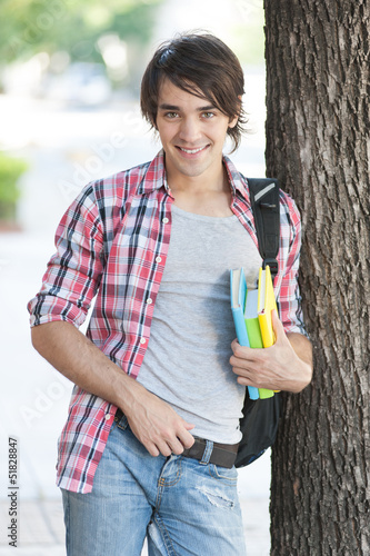 Young man holding books on the street