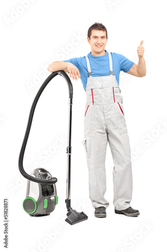 Full length portrait of a male cleaner with a vacuum cleaner giv